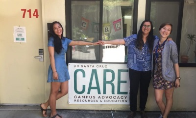 3 women, 2 are holding hands across a sign that says CARE. In front of the windows of the CARE Office.